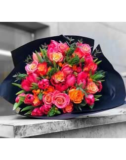 Ryški gėlių puokštė juodame floristiniame popieriuje